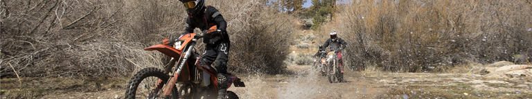 Dirt bikers ripping through the wet terrain with Fox Legion Offroad